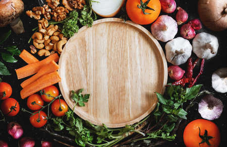 Wooden dish surrounding with fresh healthy food, on black background