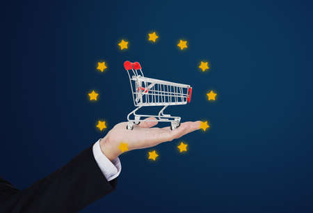 Businessman holding shopping cart, with rating stars, on blue background Imagens