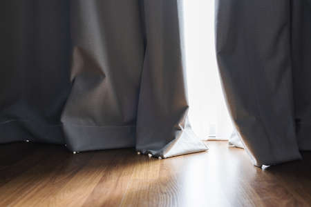Wooden floor with bright sunlight through curtain in living room Imagens