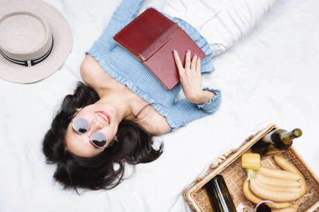 Happy woman with smiling face holding book with lunch box