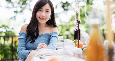 Beautiful Asian woman with smiling face, sitting at dining table