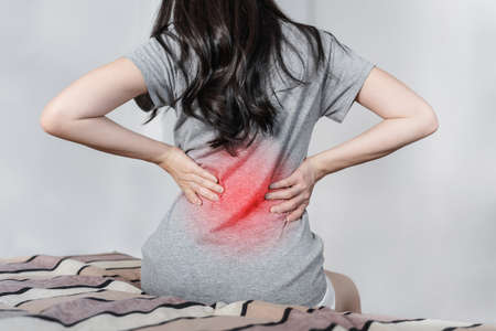Backache and Lower back pain concept. Young woman suffering from back pain, on bed after waking up Imagens