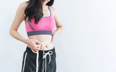 Dieting and weight loss concept, Woman with slim and healthy body using measurement tape Imagens