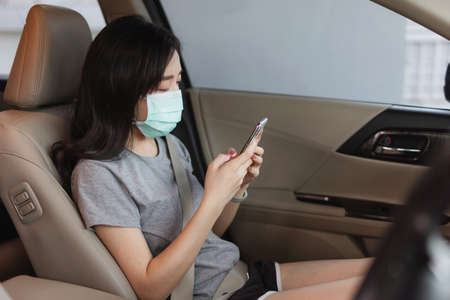 Asian woman wearing protective face mask and using mobile smartphone in modern car. New normal, corona virus and air pollution concept Foto de archivo
