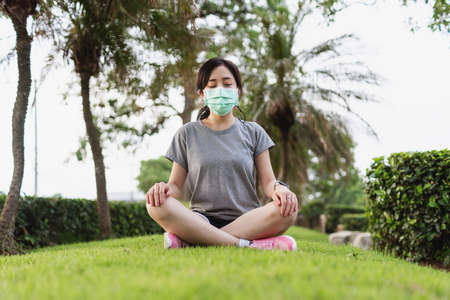 Young Asian woman wearing face mask and meditating in park