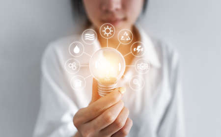 Businesswoman holding glowing light bulb, with eco-friendly energy resources icons