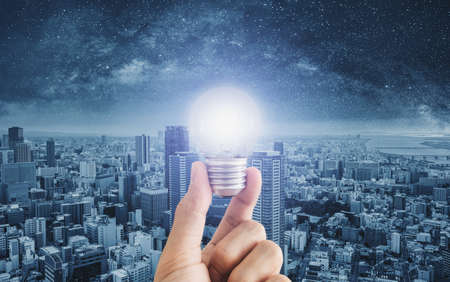 Hand holding glowing light bulb, with futuristic city background