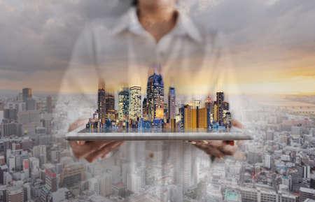 Double exposure businesswoman holding digital tablet with building hologram and city sunrise background Foto de archivo