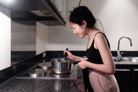 Young woman cooking in home kitchen, with smiling face