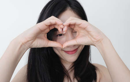 Young woman making heart shape by hands, with smiling face 版權商用圖片