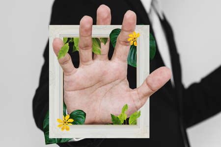 Businessman hand with picture frame, and flowers with leaves. Digital collage modern art