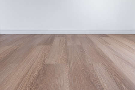 Wooden floor with white wall and floor skirting