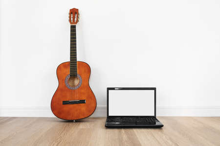 Computer laptop, blank white screen with acoustic guitar, on wood floor