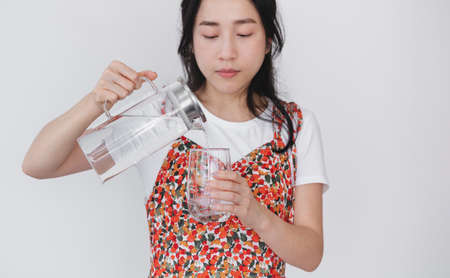 Healthy beautiful young Asian woman, pouting fresh water on drinking glass, on white background 版權商用圖片