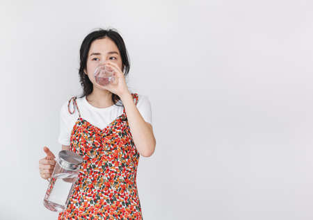 Healthy beautiful young Asian woman, drinking water, on white background