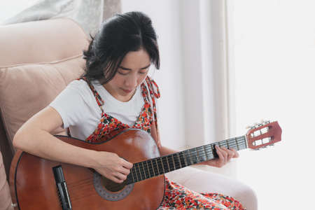 Young Asian woman play guitar. Home hobbies and recreation 版權商用圖片