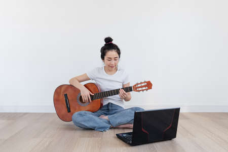 Young Asian woman play guitar, with computer laptop in living room. Home hobbies and recreation, Online training and learning class