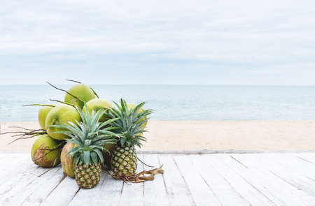 Summer background, coconuts and pineapples on white wood table, on the beach in summer