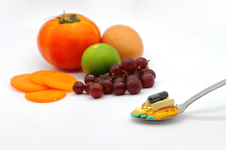 Assorted vitamins and nutritional supplements in serving spoon on blur colorful fruits background