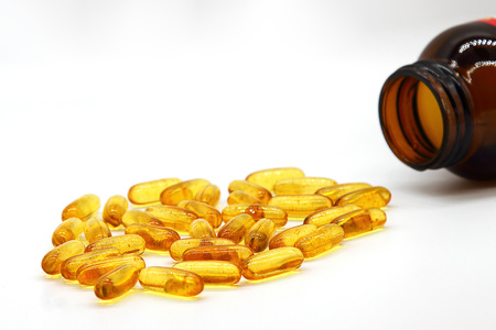 Fish oil capsules with omega 3 and vitamin D in a glass bottle on White background