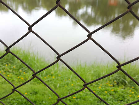 mesh fence: Mesh fence with the green grass and the river Background.