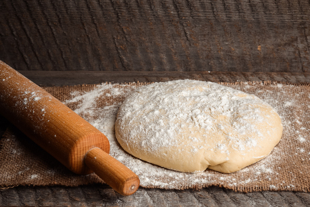 Ball of pizza dough and a rolling pin on a rustic wooden background with dusting of flour Stock Photo