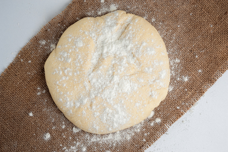 proved: Ball of pizza dough on a rustic wooden background with dusting of flour