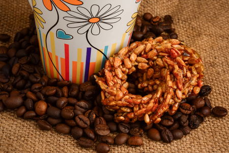 Cup of coffee, biscuits and coffee beans on a wooden background closeup