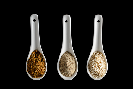 three porcelain spoons with spices on a black background isolated. Top view