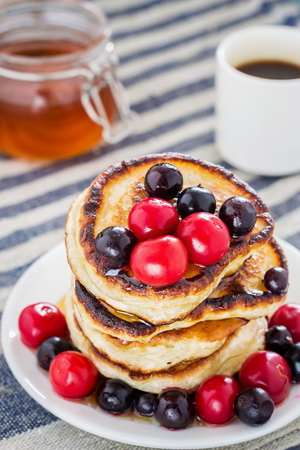 white plate full of pancakes with berries and honey on a wooden background top view