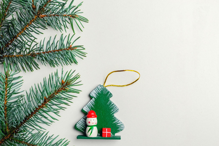 a toy for a Christmas tree and a spruce spruce on a white background. Place for text. New Years decoration. Toy tree and snowman Stock Photo