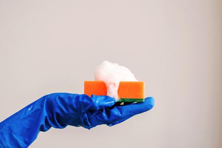 泡とオレンジのスポンジは、あなたの手のひらの上にあります。はめた手がスポンジを握る