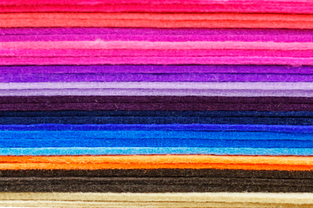 Multicolored strips of cloth lying horizontally on each other. Texture of colored striped fabric