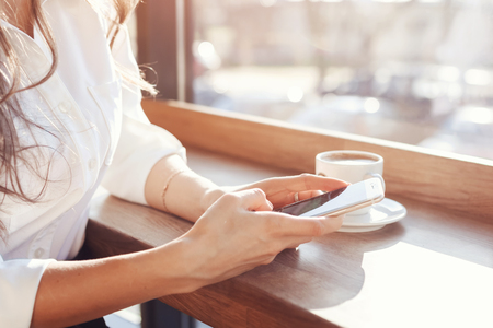 a girl in a white blouse is sitting at a wooden table in a cafe, drinking coffee and holding a phone. Archivio Fotografico