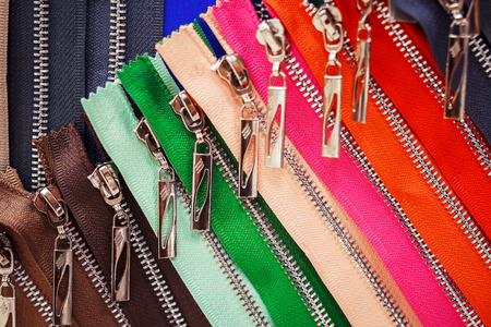 a lot of bright colored zippers for clothes in the store. zippers for clothes are lined up.