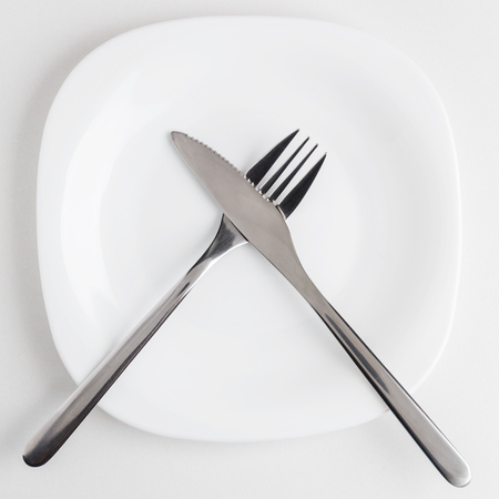 cutlery, fork and knife on an empty white plate Stock Photo