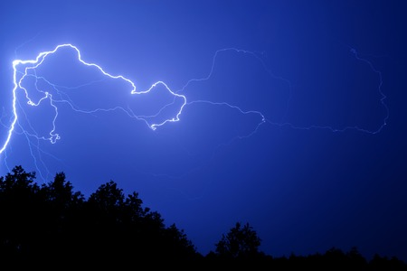 bright lightning on a blue sky at night over the trees. Foto de archivo