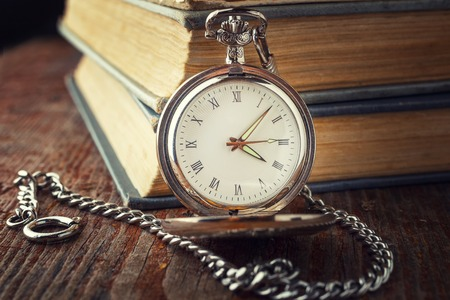 vintage watch on a chain on a background of old books. Toned photo in a dark key