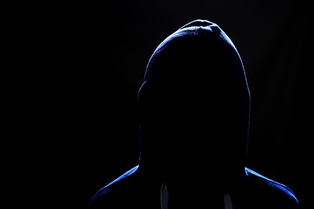 faceless human figure in a hood on a black background. The concept of cybercrime, theft in the network. A dangerous, sinister person.