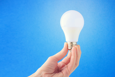 LED lamp in hand on a blue background. Concept of the idea. Copy space Stock Photo