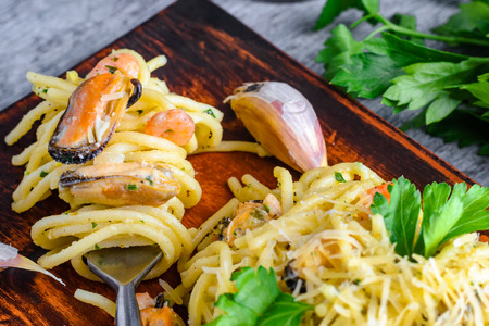 Pasta with seafood mussels and shrimps in a creamy sauce and a bunch of parsley on a plate.