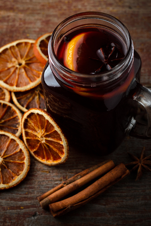 homemade mulled wine, dried oranges and cinnamon sticks on a wooden table on a dark background. Top view Stock Photo
