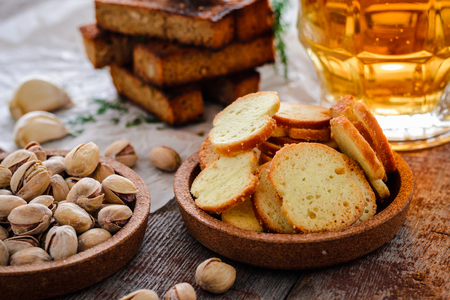 Beer in a glass, pistachios, rye croutons with dill and crackers on a wooden table Stock Photo