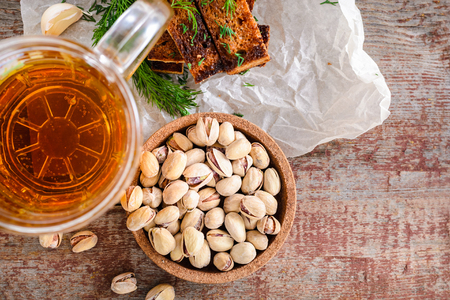 A glass of light beer, garlic rye toast with a dill and pistachios on a wooden table. Top view Stock Photo