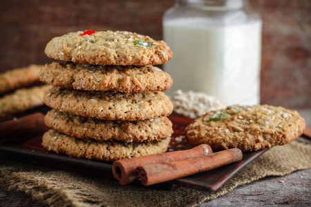 Homemade oatmeal cookies, stacked, cinnamon sticks and a glass of milk on a wooden background Stock Photo
