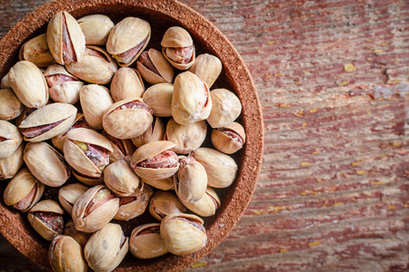 A bunch of pistachios in a plate on a wooden table. Top view with copy space