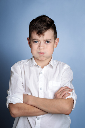 Closeup portrait of angry young boy isolated on blue background.