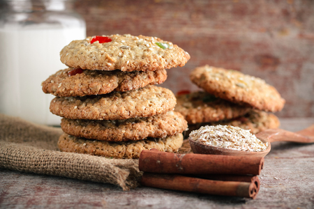 Homemade oatmeal cookies and a mug of milk on a wooden table