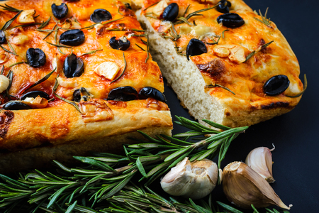 Italian focaccia with rosemary and olives on a black wooden table. Stok Fotoğraf - 94926325