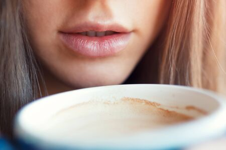 A close-up of a girl drinks her lips with a cup of coffee. Toned photo Banque d'images